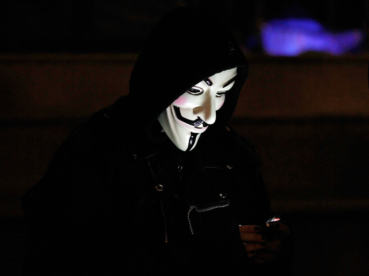An anti-corporate protester's mask is lit by the light from her mobile phone in Oakland, California, November 11, 2011. (Photo by Kim White/Reuters)
