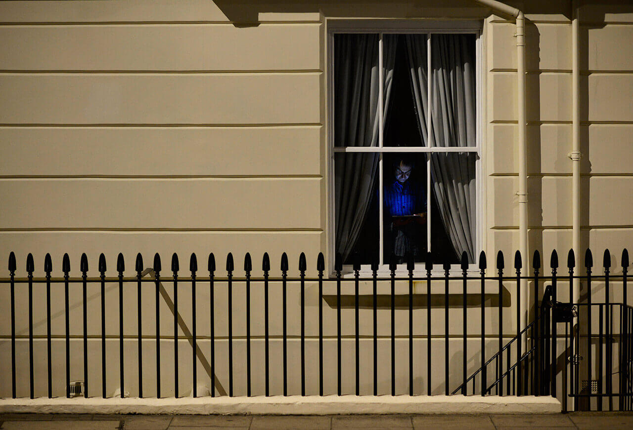 A man is illuminated by his tablet as he stands by his window on a warm spring evening in Westminster, London, May 11, 2015. (Photo by Dylan Martinez/Reuters)
